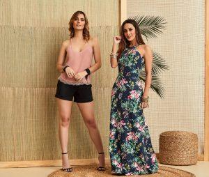 Duas mulheres, uma com vestido longo outra com shorts de alfaiataria.