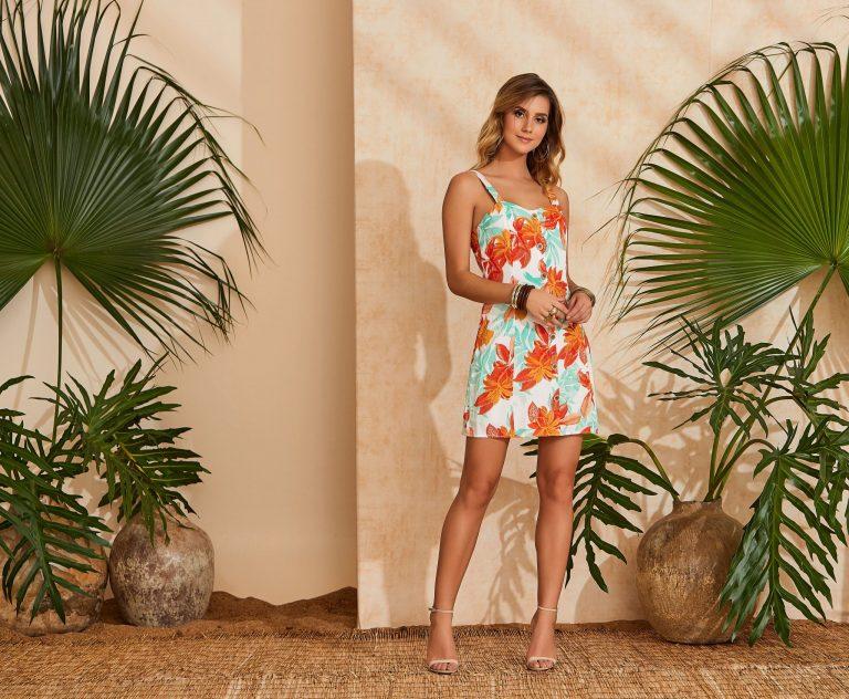 Mulher vestindo uma tendência de moda verão 2020, um vestido tropical laranja e branco