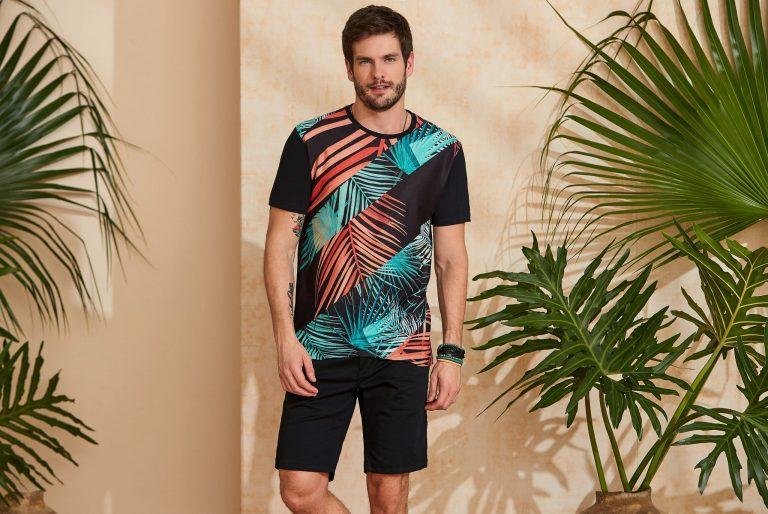Modelo vestindo peças da moda masculina Verão 2020: camiseta tropical e bermuda preta