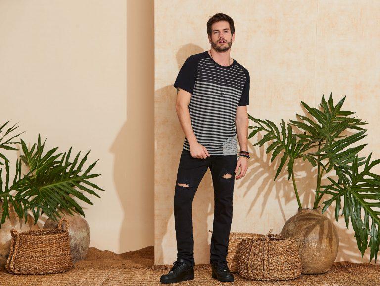 Modelo vestindo peças da moda masculina Verão 2020: camiseta listrada e calça rasgada