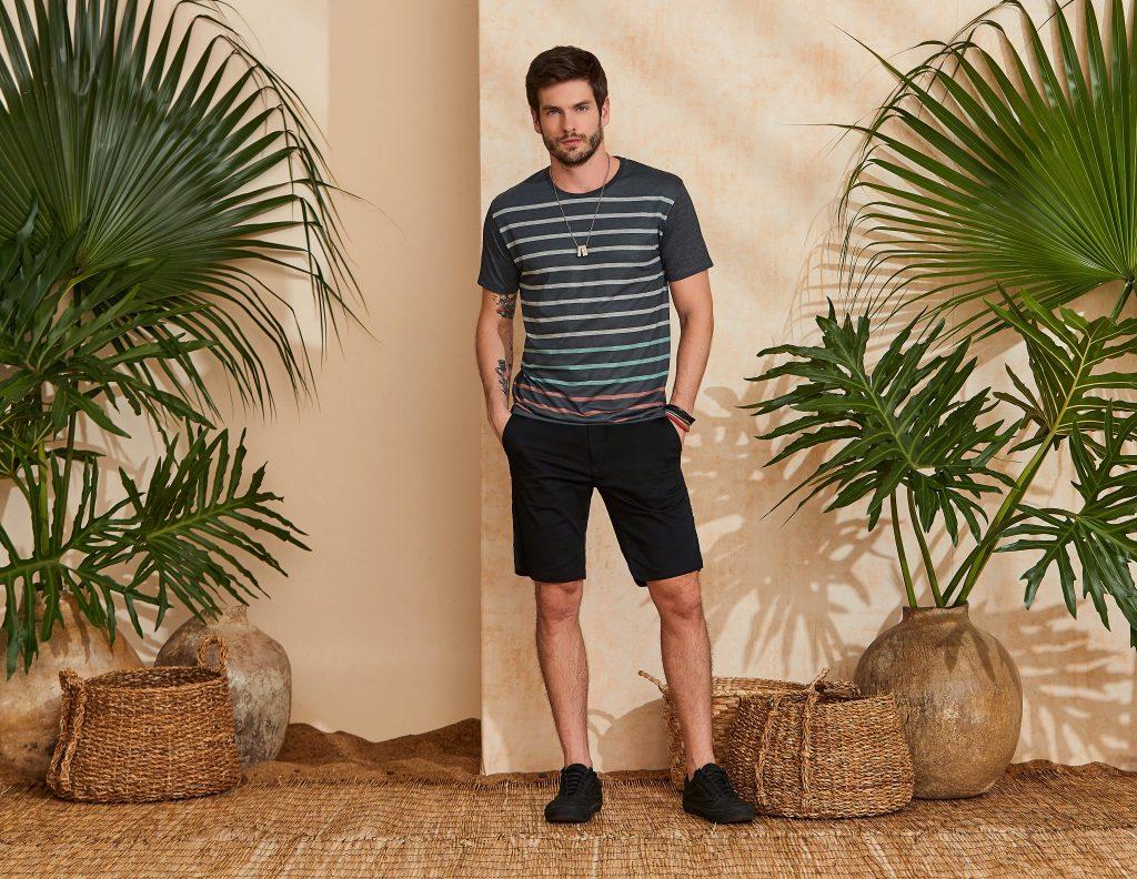 Modelo vestindo peças da moda masculina Verão 2020: camiseta listrada e bermuda preta