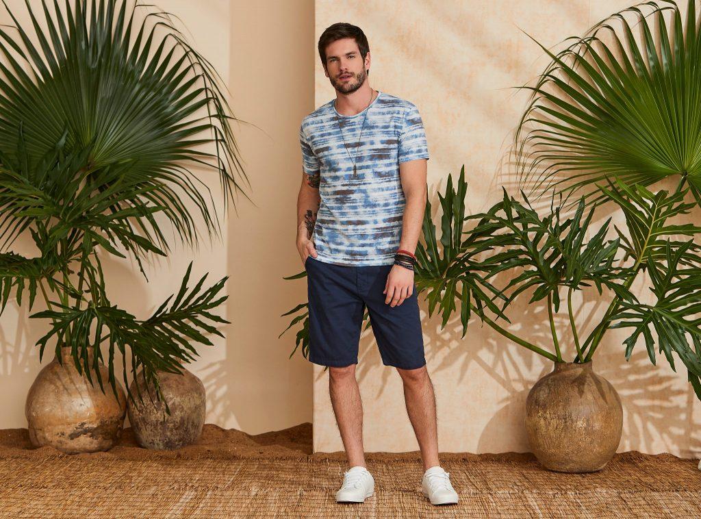 Modelo vestindo peças da moda masculina Verão 2020: camiseta tie dye listrada e bermuda azul