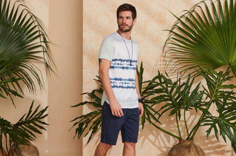 Modelo vestindo peças da moda masculina Verão 2020: camiseta tie dye e bermuda azul