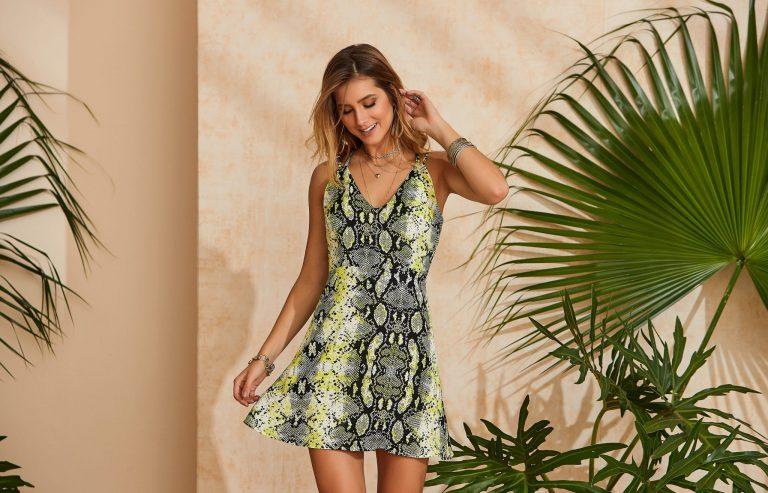 Modelo com cores verão 2020:  vestido com estampa de cobra e detalhes verde neon